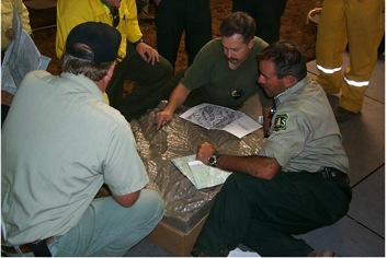 Figure 12. Management team discussing tactics using a solid terrain model on the Kirk Fire LPF 1999 (21)